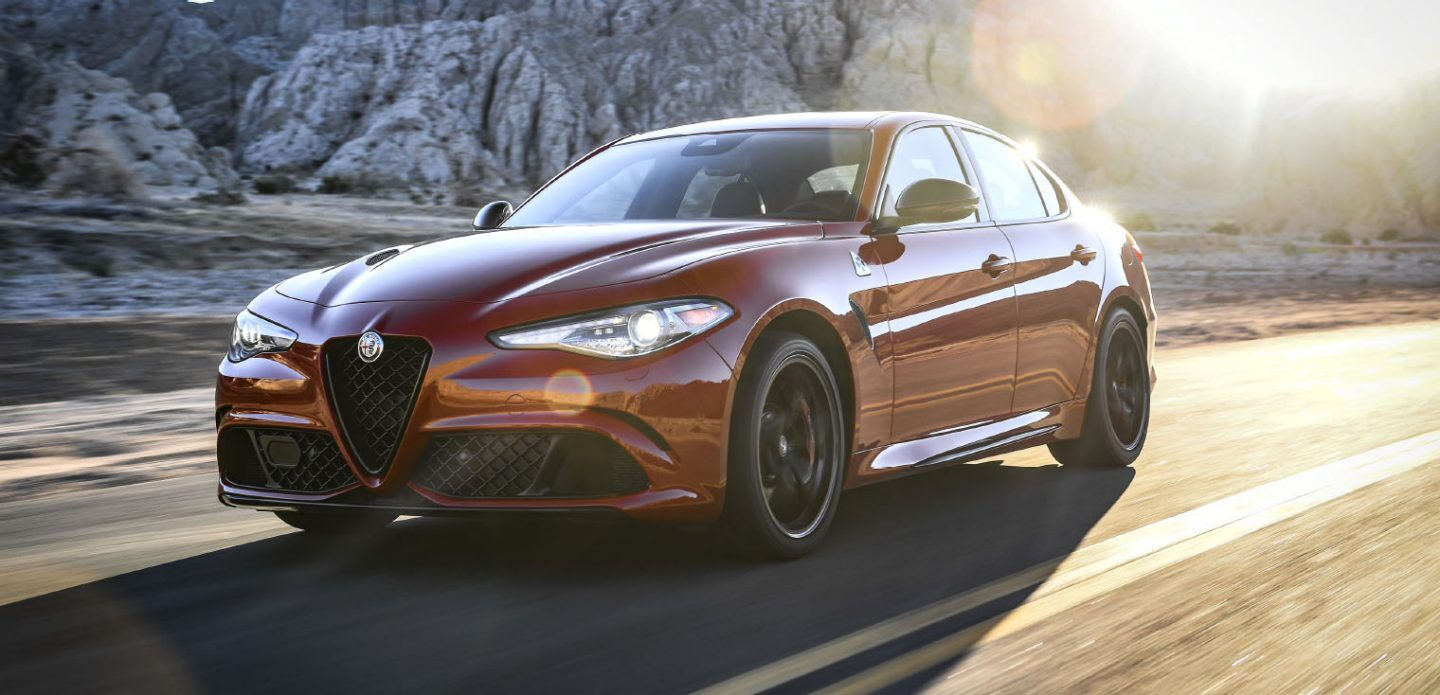 Display An angled profile view of a red 2021 Alfa Romeo Giulia Quadrifoglio with its headlamps on, being driven on a highway near rock formations at sunset.